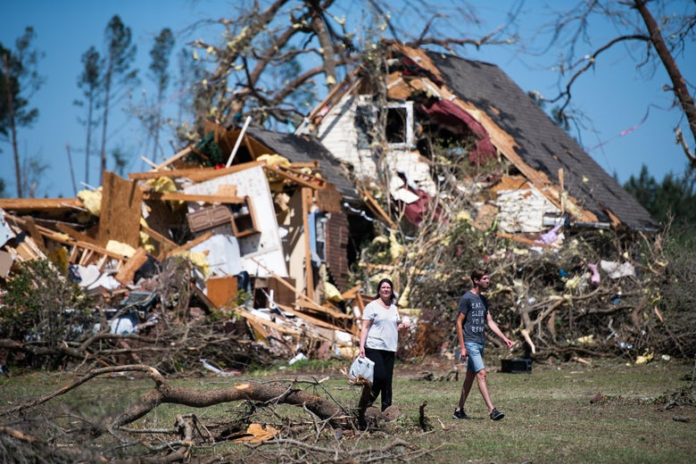 Two women walk in front of a destroyed house and felled trees
