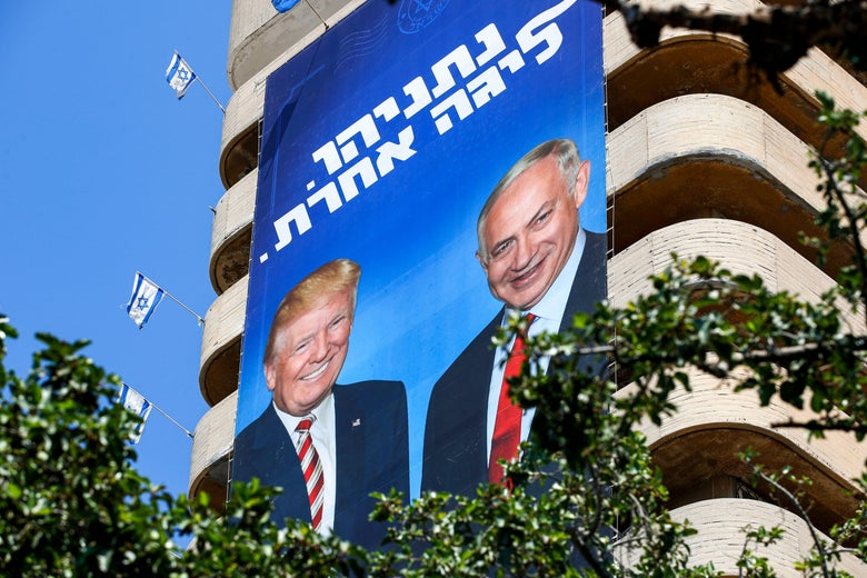 A giant Israeli Likud party election banner hanging from a building shows Benjamin Netanyahu with Donald Trump.