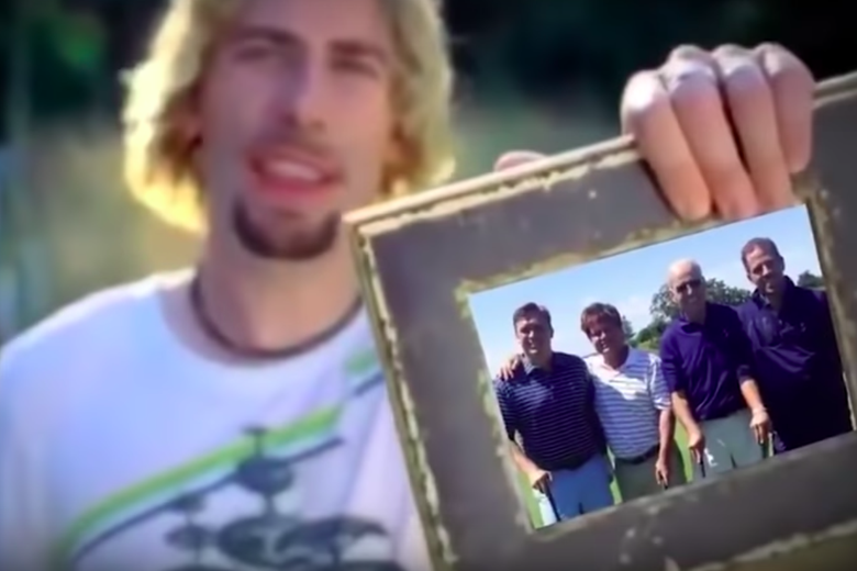 A blurry Chad Kroeger holds a picture frame with an image of four people in it. Two of them are Joe and Hunter Biden.