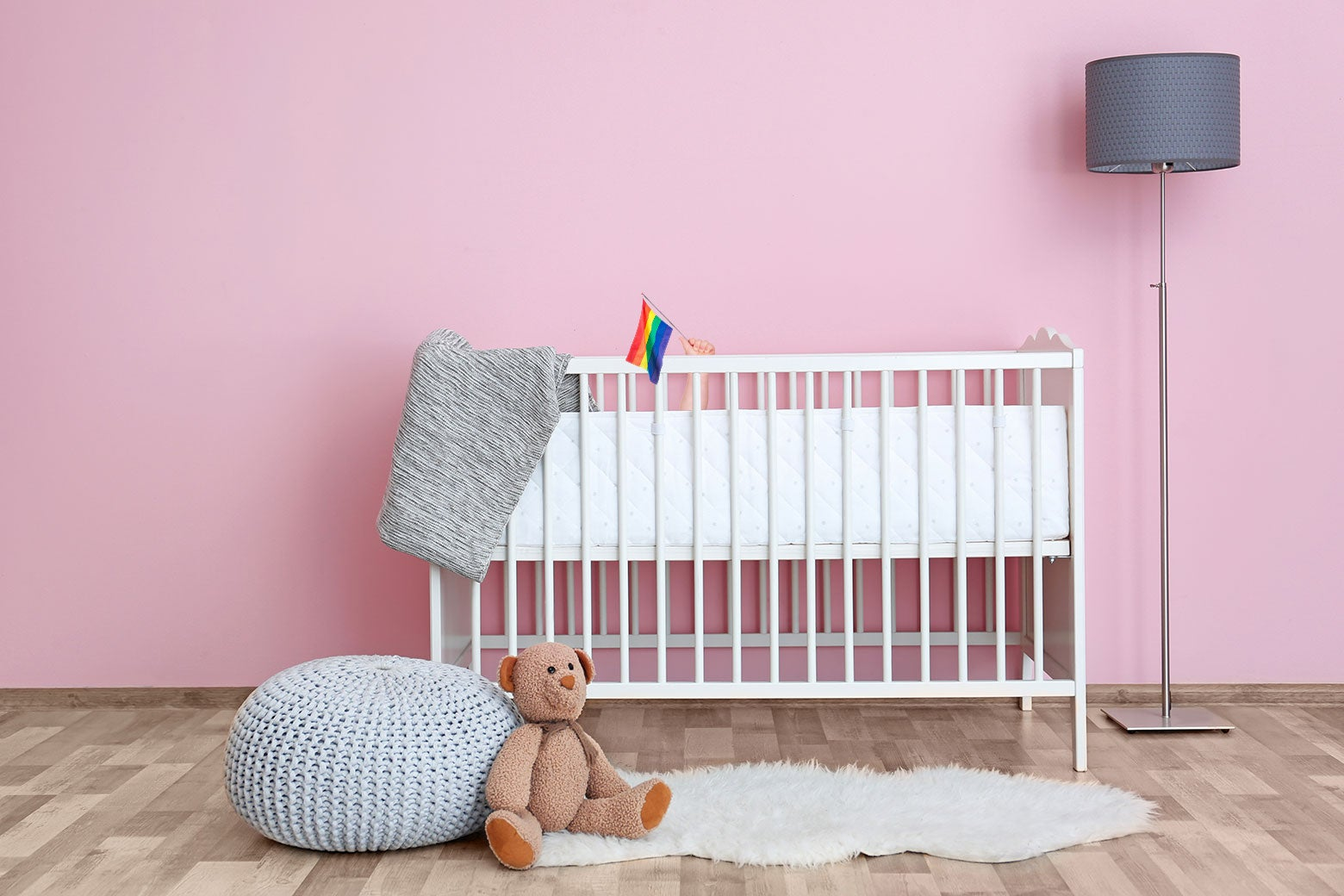 Photo illustration of a baby crib with a little pride flag poking out of it.