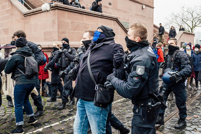 Police stand between Querdenken supporters and left-wing counterprotesters. In the foreground, two officers hold a man by both arms.