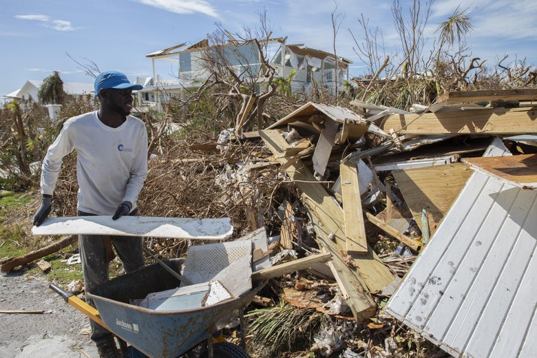 A resident collects rubble and debris from damaged homes after Hurricane Dorian devastated Elbow Key Island.