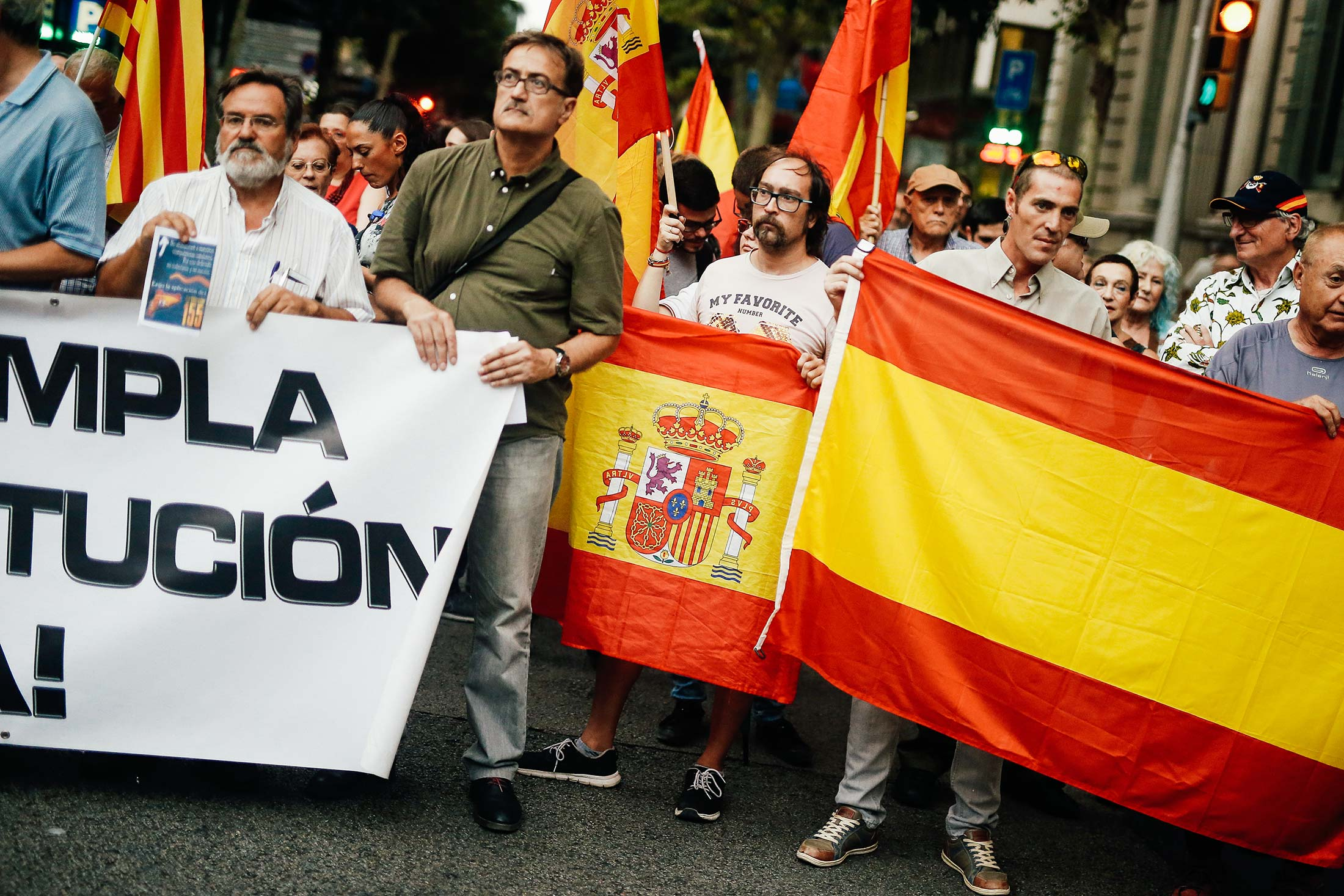 Men hold Spanish flags, signs, and a banner.