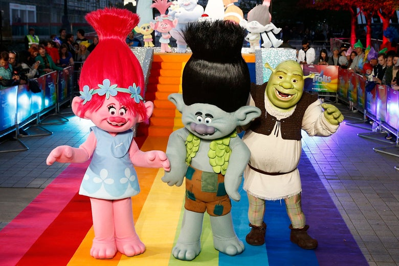 Two people dressed in mascot costumes as trolls from the animated movie Trolls, plus one person dressed as Shrek, walking down a rainbow carpet at a Trolls photocall.