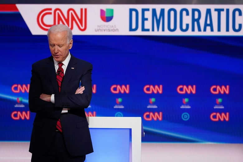 Joe Biden stands onstage with his head downcast and his arms crossed