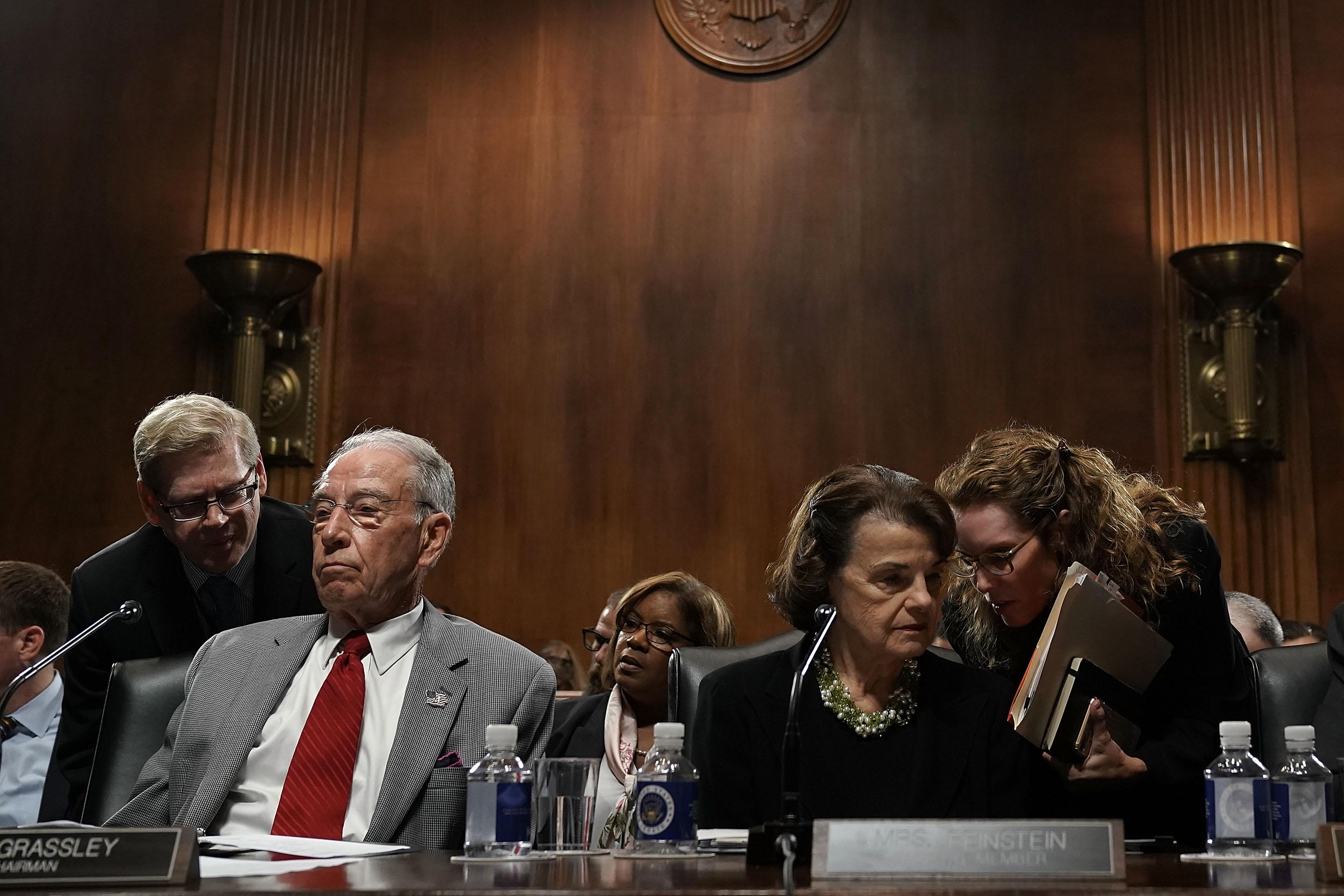 Aides lean in to talk to Sens. Chuck Grassley and Dianne Feinstein during a hearing.