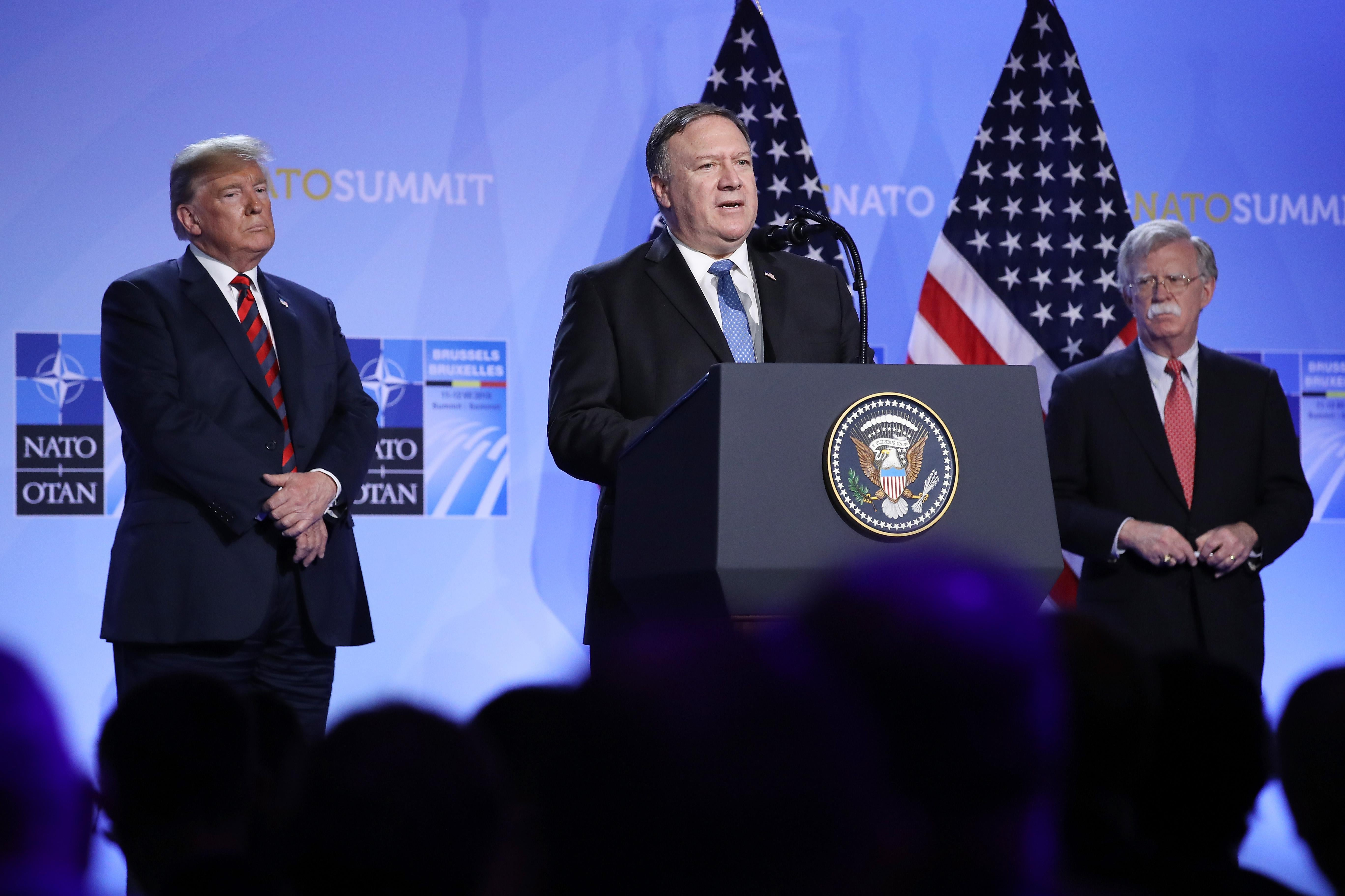 U.S. President Donald Trump (L) and National Security Advisor John Bolton (R) look on as U.S. Secretary of State Mike Pompeo speaks briefly to the media at a press conference on the second day of the 2018 NATO Summit on July 12, 2018 in Brussels, Belgium.