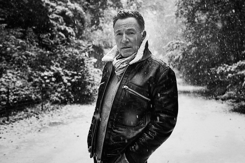 A black-and-white photo of  Bruce Springsteen standing in a snowy woods.