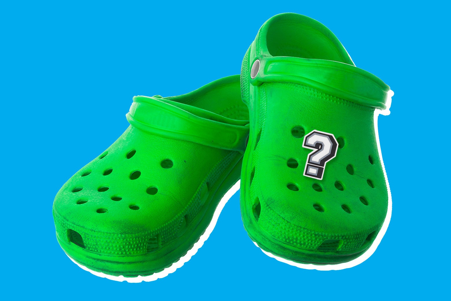 A pair of green Croc clogs with a question-mark button.