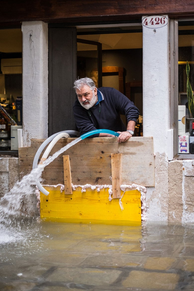 A man pumping water out of his flooded restaurant in Venice.
