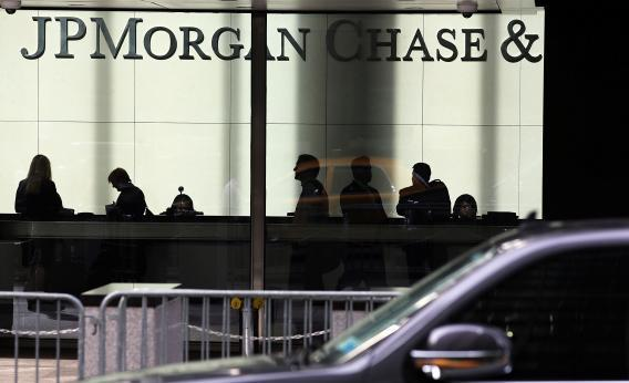 People pass a sign for JPMorgan Chase & Co. at its headquarters in Manhattan on Oct. 2, 2012, in New York City.
