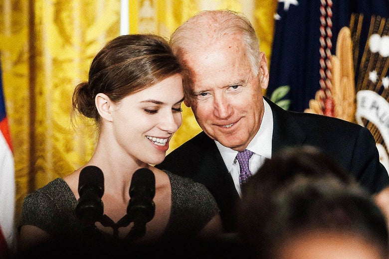 "Lilly Jay, a survivor of sexual assault, stands with Vice President Joe Biden at the launch of the ""It's On Us"" campaign at the White House on Sept. 19, 2014. Biden is leaning close enough that his head is almost touching Jay's."