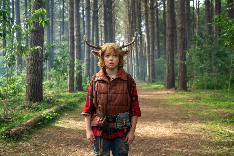 Actor Christian Convery as Gus, a boy with antlers on his head, standing in the woods in a still from Sweet Tooth.