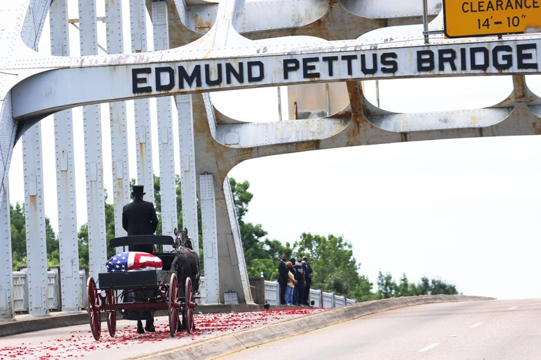 A horse-drawn carriage carrying the body of civil rights icon, former US Rep. John Lewis (D-GA) crosses the Edmund Pettus Bridge as it prepares to pass members of his family on July 26, 2020 in Selma, Alabama.