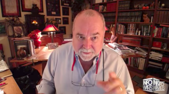A balding man with a grey beard leans toward the camera in what appears to be a home office/library.