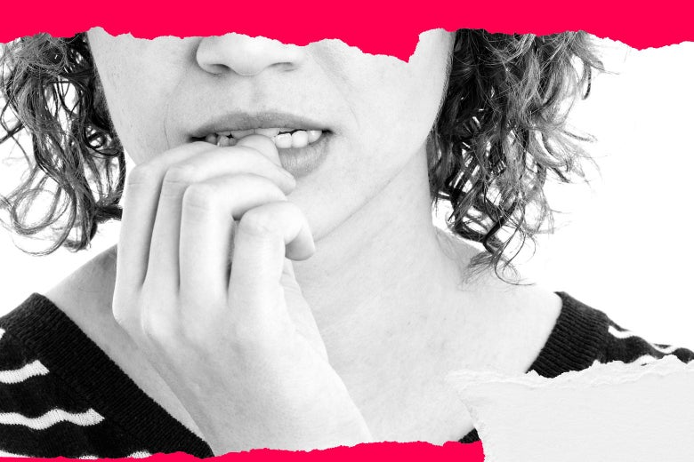 A woman looks anxious, biting her nails.