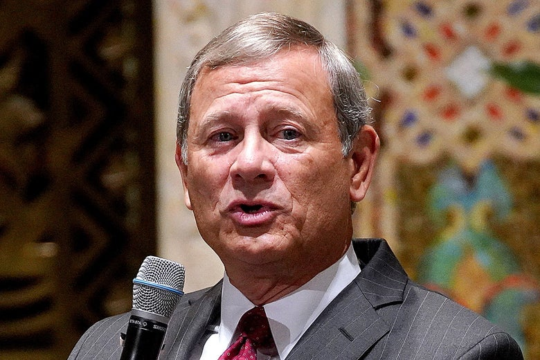 Roberts speaking into a microphone.