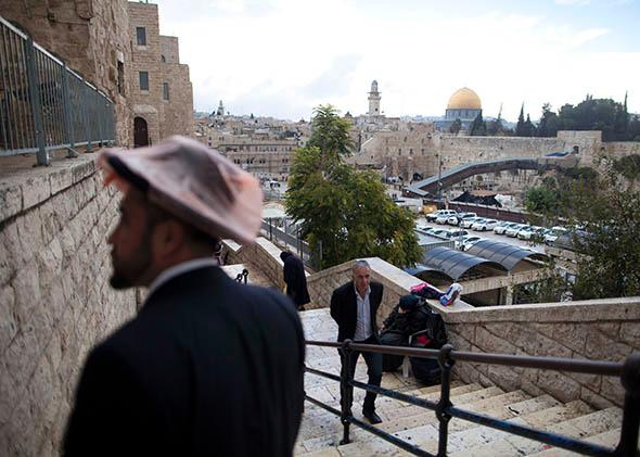 Israelis walk at the Jewish quarter in the Old City overlooking the Temple Mount compound with The Dome of the Rock.