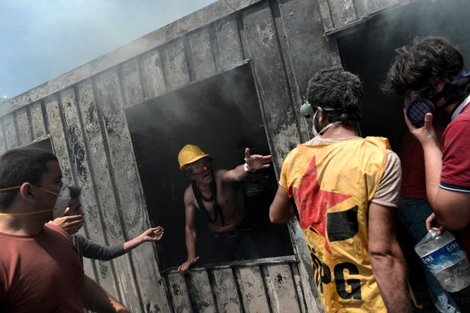 Demonstrators try to extinguish a fire in a container used for construction workers in Taksim Square in Istanbul on June 4, 2013.