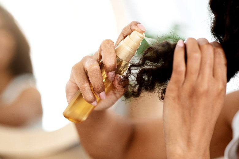 A Black woman spraying the ends of her hair.