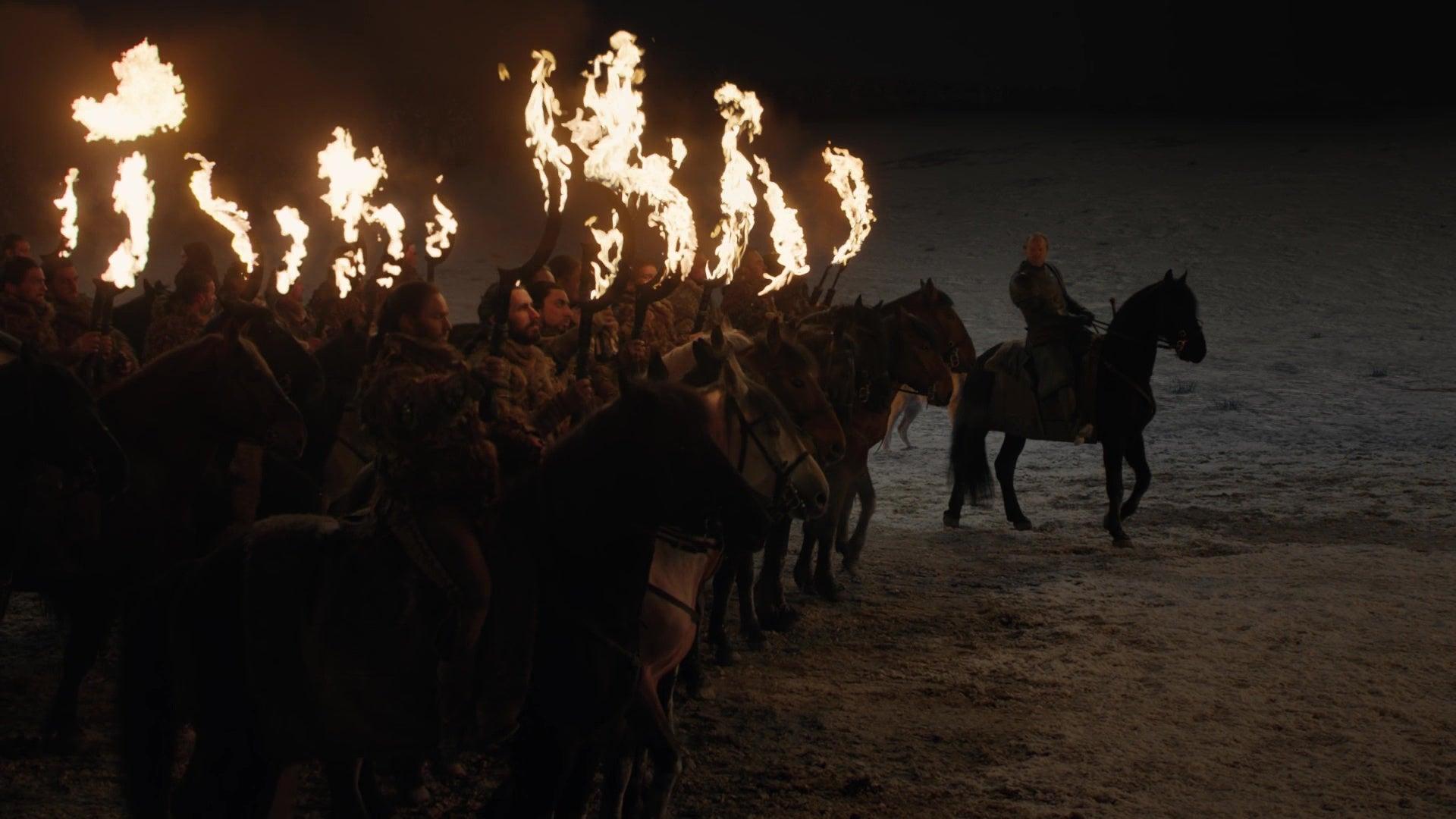 A group of Dothraki warriors on horseback hold up their flaming swords.