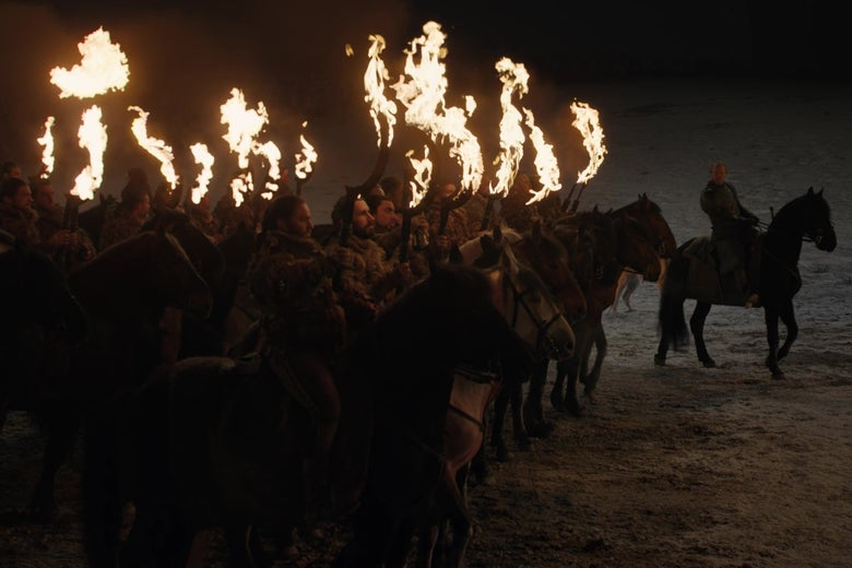 A group of Dothraki warriors on horseback hold up their flaming swords.