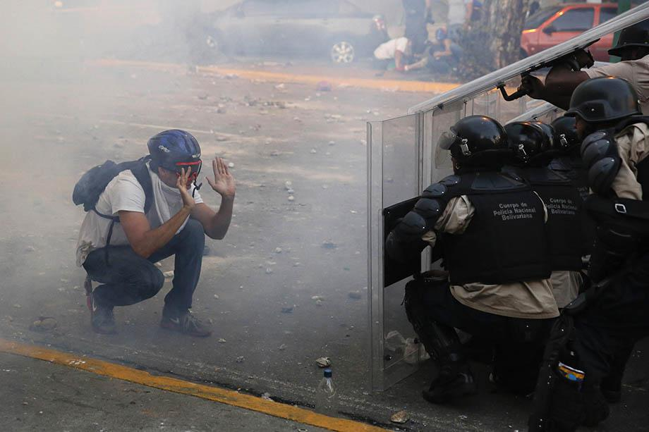 An opposition demonstrator confronts riot police during a protest against President Nicolas Maduro's government in Caracas.