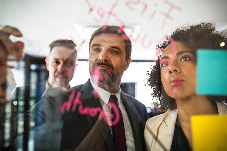 Two white men and one black woman sticking paper on glass board