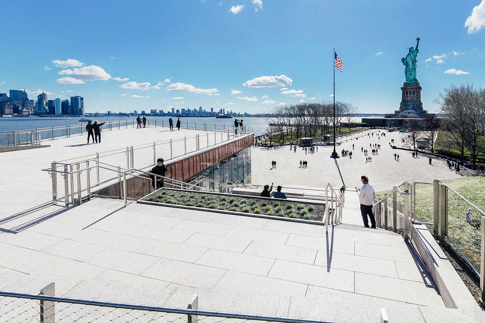 Statue of Liberty Museum pavilion, with the statue and the New York skyline in the background.