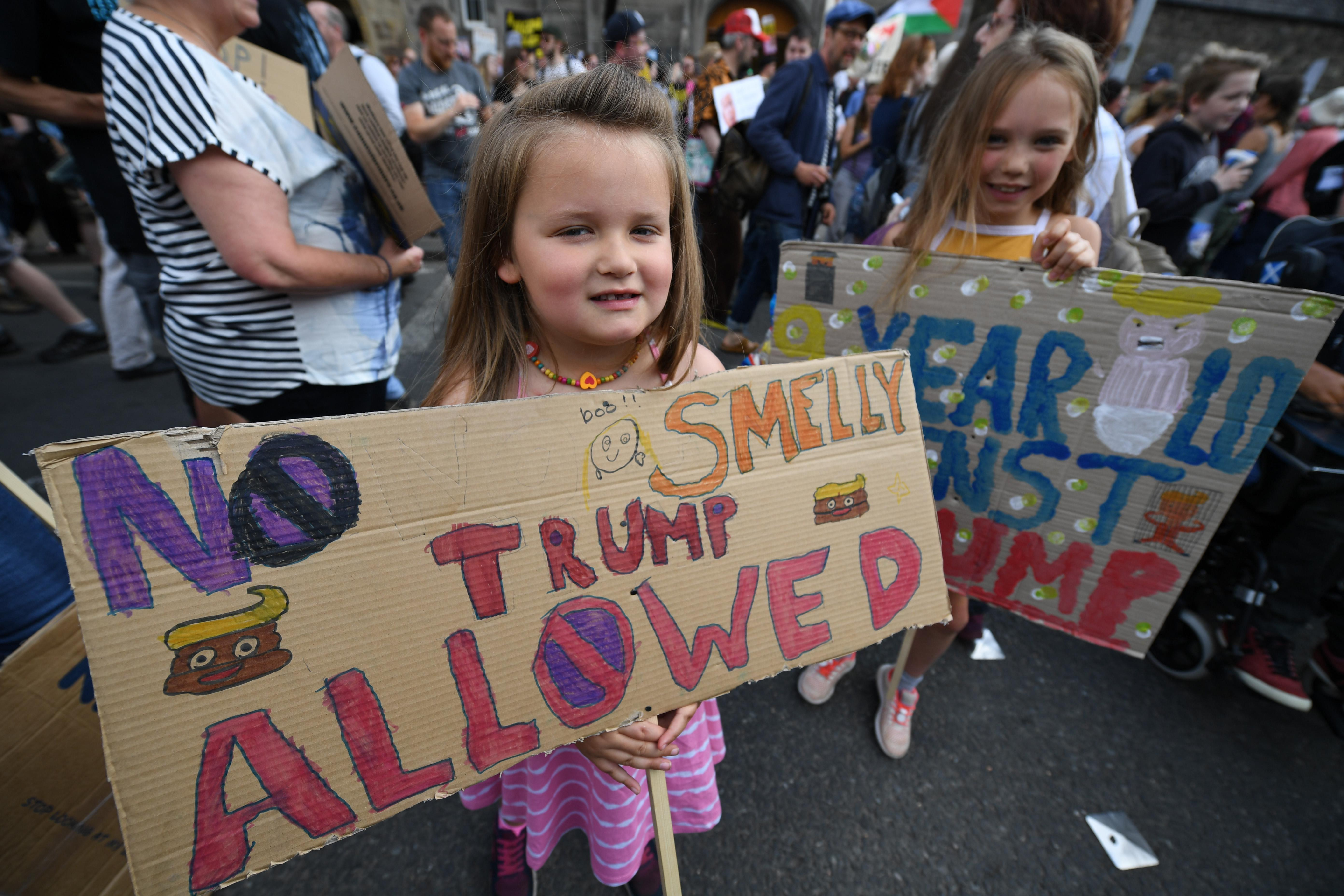 Young girls hold anti-Trump signs on July 14, 2018 in Edinburgh, Scotland.