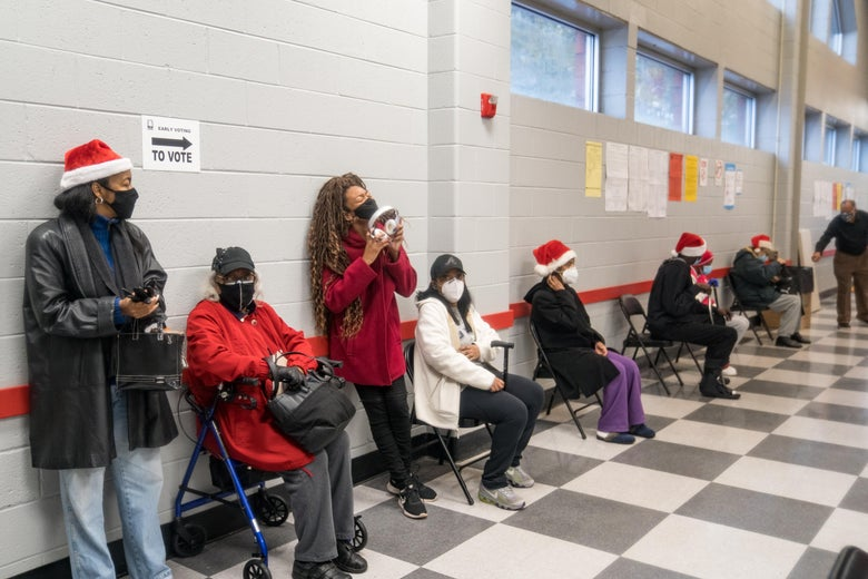 People wait in a socially distanced line in a hallway, some standing against the wall, others sitting on folding chairs. All are masked. Some are wearing Santa hats.