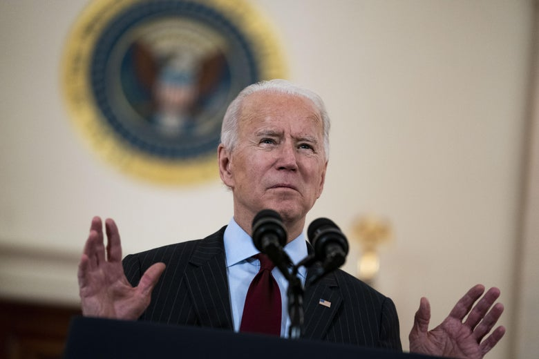 Biden raises his hands while speaking into two microphones.