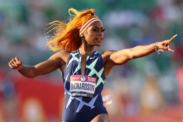 A woman with orange hair points in triumph at the Olympic trials.
