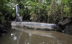 Colombian soldiers guard a homemade submersible in a rural area of Timbiqui, department of Cauca, Colombia. Click image to expand.