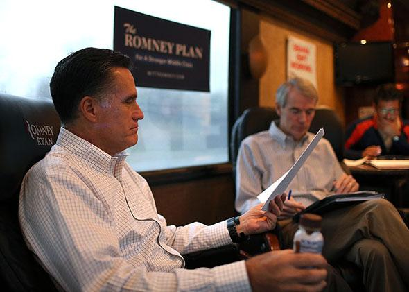 Mitt Romney looks over documents with campaign adviser Sen. Rob Portman on his campaign bus en on Oct. 29, 2012 in Avon Lake, Ohio.