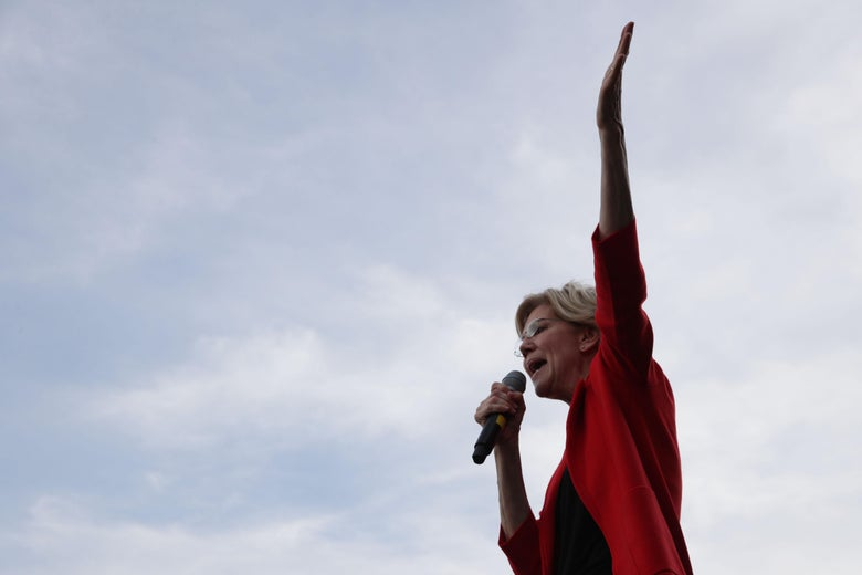 Sen. Elizabeth Warren, wearing a red blazer and holding one arm aloft, speaks onstage during a campaign town hall.