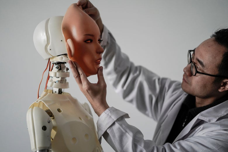 An engineer attaches a rubber face to a not-very-convincing-looking sex robot.