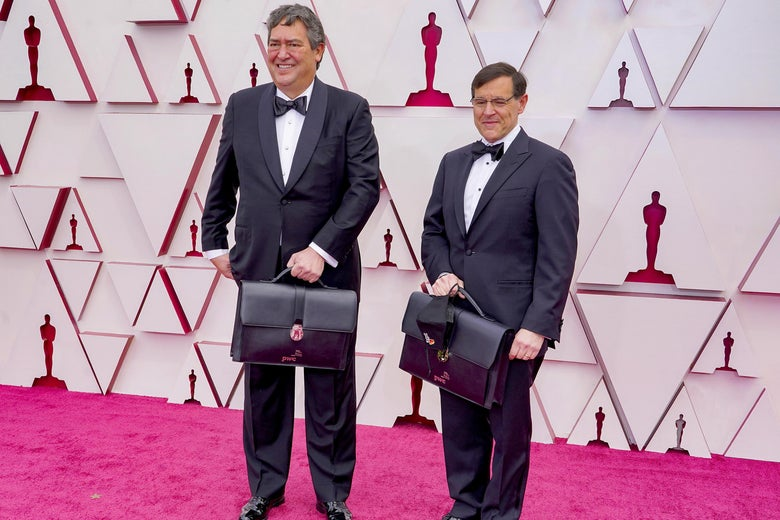 Two PricewaterhouseCoopers employees on the Academy Awards red carpet, holding briefcases with the winners.