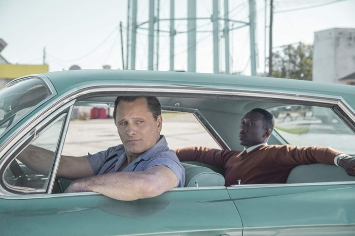Two men in a light, blue-ish green car. One man is sitting in the front seat with his elbow out the window. The other is in the backseat, arms stretched across.
