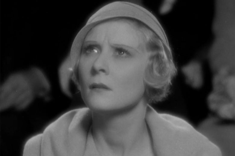 Actress Peg Entwistle, in a cloche hat and matching jacket, looking concerned.
