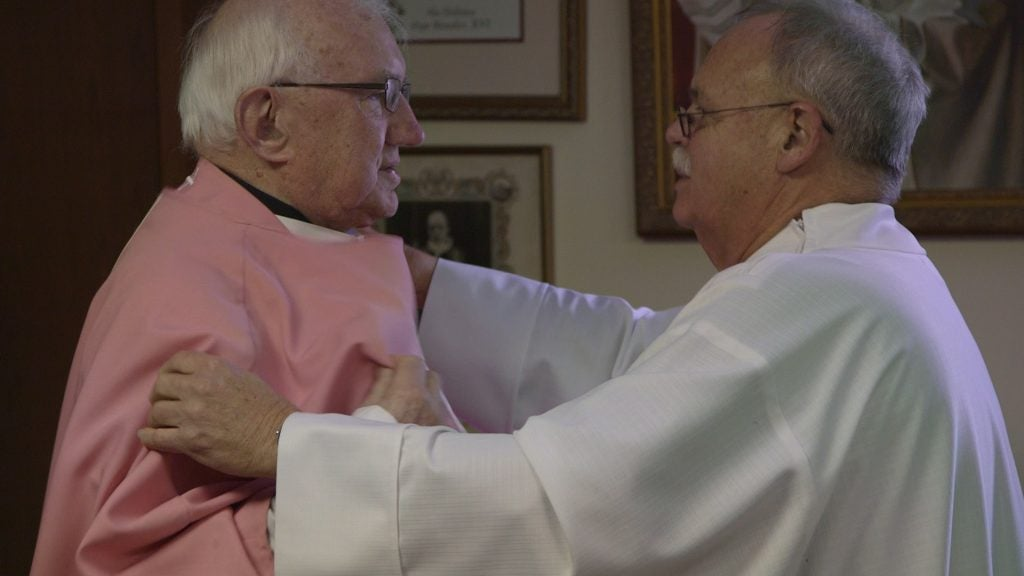 Father Bob Weiss and Father Basil O'Sullivan prepare for the one-year anniversary of the Newtown school shooting. They are both elderly priests: O'Sullivan, on the left, is in his seventies, while Weiss, right, is probably in his fifties or early sixties.