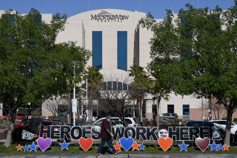 "A man walks by a sign reading ""Heroes work here"" outside MountainView Hospital on April 2."