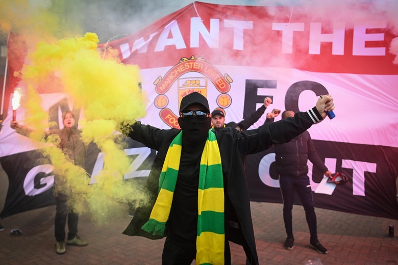 A Manchester United fan holds a flare in front of an anti-Glazer banner.