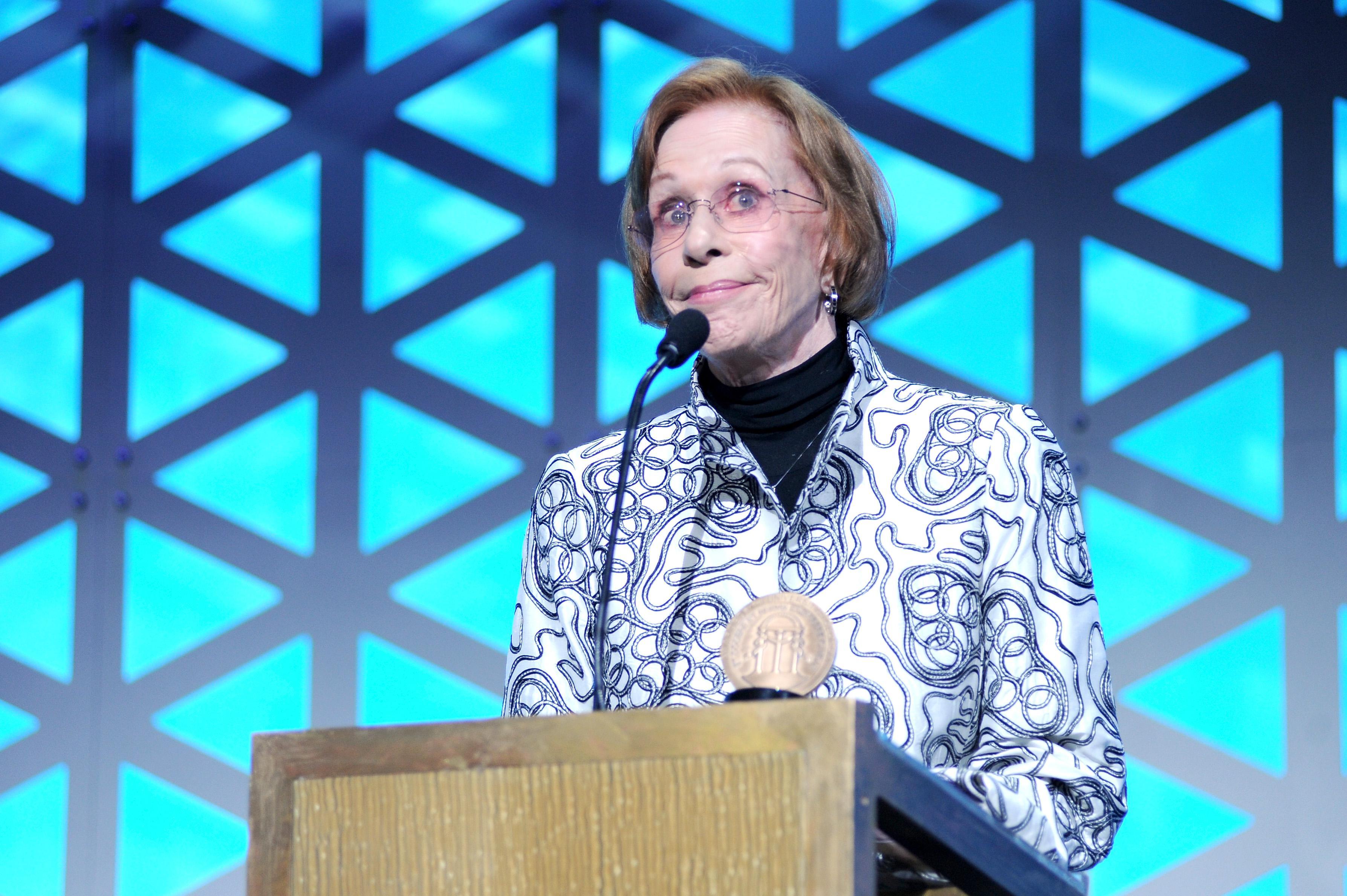 Carol Burnett stands at a podium.