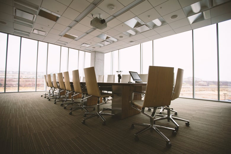 A long, empty conference room table in a corner room with floor-to-ceiling windows.