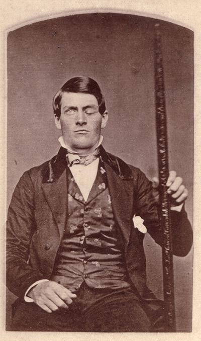 Cabinet-card portrait of Gage shown holding the tamping iron which injured him.