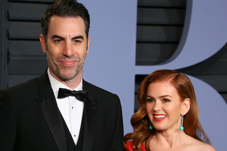 Sacha Baron Cohen and Isla Fisher on a red carpet. He is a head taller than she is.