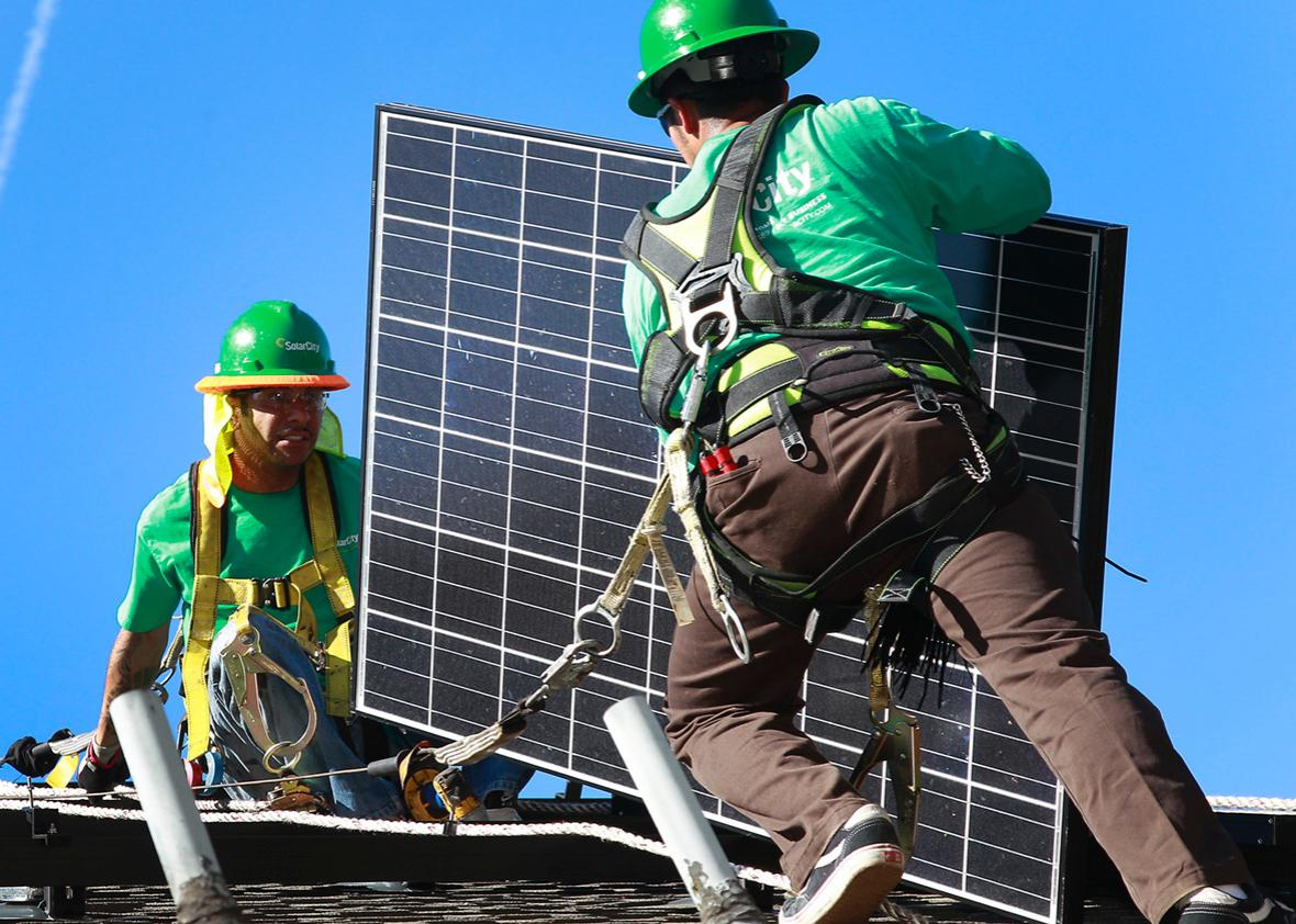 Lead installers for SolarCity, Charles Groves, right, and Matt Parra, install solar panels on the roof of a home on March 31, 2011, in Palo Alto, California