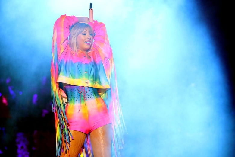 Taylor Swift on stage in a rainbow outfit.