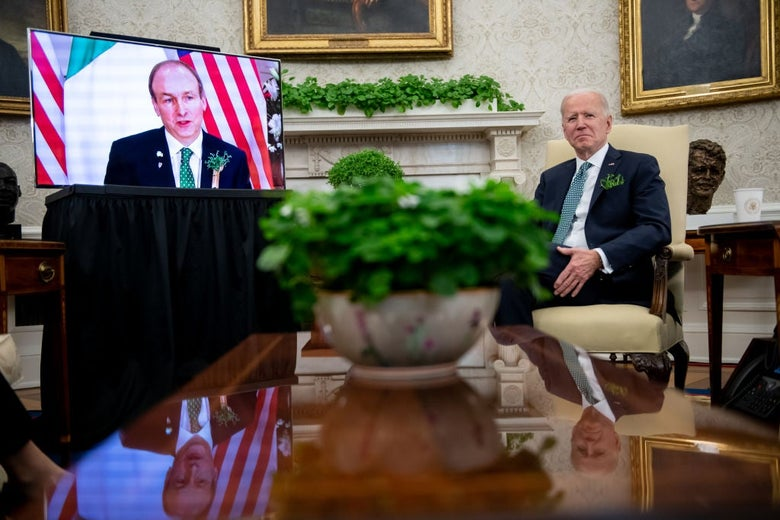Biden sits in the Oval Office next to a large TV screen on which Martin appears.